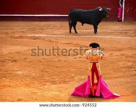 Bullfighter and bull in a standoff - stock photo