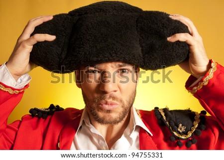 Bullfighter putting on big montera hat humor spanish colors - stock photo