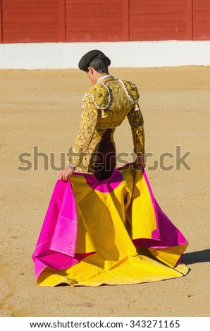 bullfighter standing and holding the capote. Matador in the bullring - stock photo