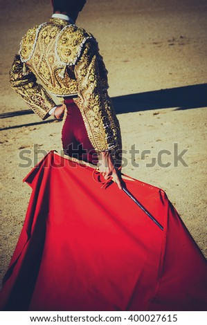 bullfighter standing and holding the capote. Matador in the bullring. Vignette effect
