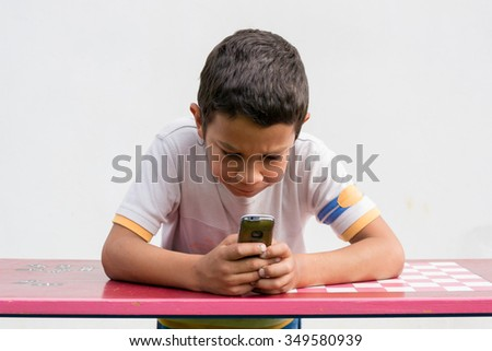 Bullied sad gypsy child boy calling home with mobile phone from school for help - stock photo