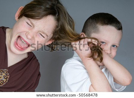 Bully boy pulling girl's hair - stock photo