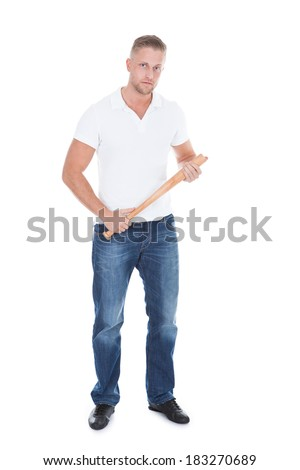 Bully or thug standing holding a baseball bat in his hands and looking at the camera with a menacing stare and threatening attitude  isolated on white - stock photo
