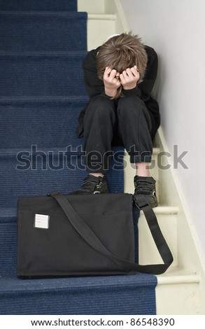 Bullying concept: Child sits on stairs holding his head in his hands.
