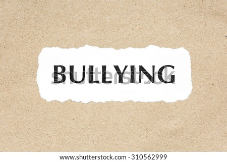 Bullying word on white ripped paper on brown document texture - stock photo