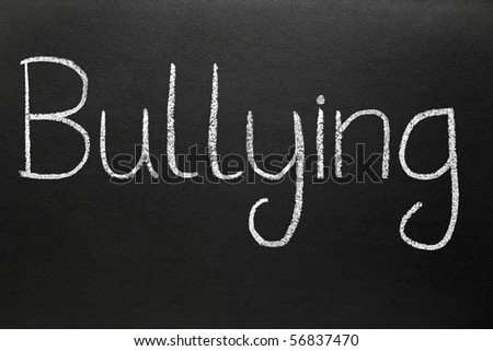 Bullying, written with white chalk on a blackboard. - stock photo