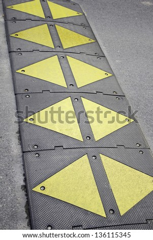 Bump on road signposted for the protection of pedestrians, and vehicle speed - stock photo