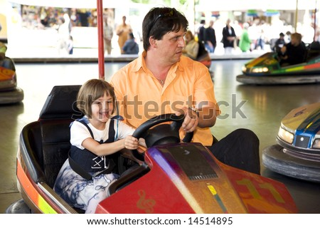 Bumper car with father and daughter on kermis - stock photo