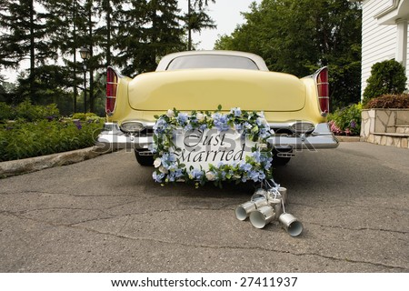 Bumper of limousine with just married sign and cans attached - stock photo