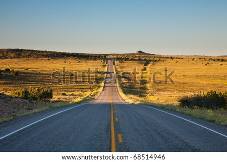 Bumpy road crossing plains at sunset - stock photo