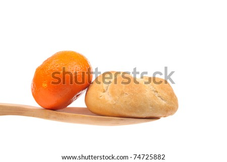 Bun and a tangerine on a wooden spoon against a white background