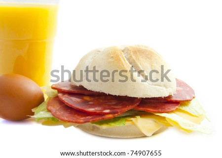 Bun with egg and juice isolated over white - stock photo