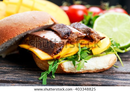Bun with grilled roast beef, mango and arugula.
