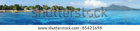 Bunaken island (left) with boats and wooden buildings in trees. North Sulawesi. Indonesia - stock photo