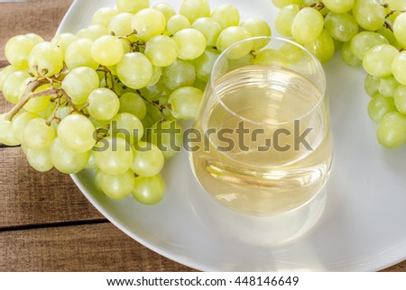 bunch green grapes with glass of  white wine on white plate, food closeup