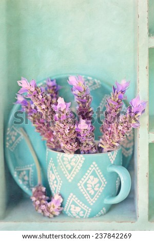 Bunch of a lavender flowers  in a blue tea mug .Vintage background . - stock photo