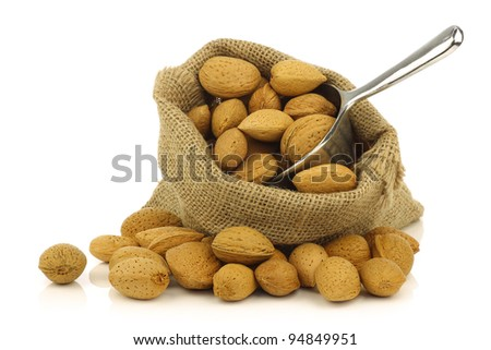 bunch of almond nuts in a burlap bag with a metal scoop on a white background