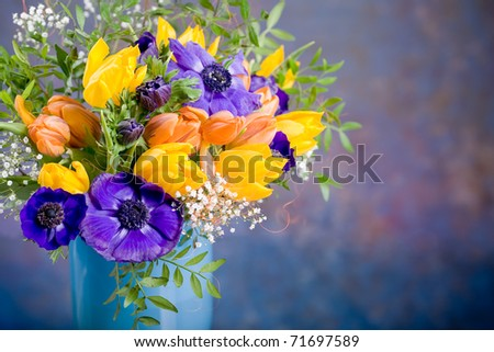 bunch of anemones and tulips on the table - stock photo