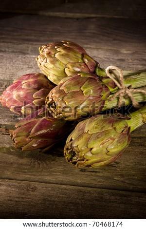bunch of artichoke on wood background - stock photo