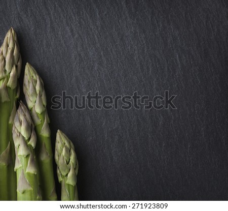 Bunch of asparagus isolated on dark grey slate stone with empty copyspace. - stock photo