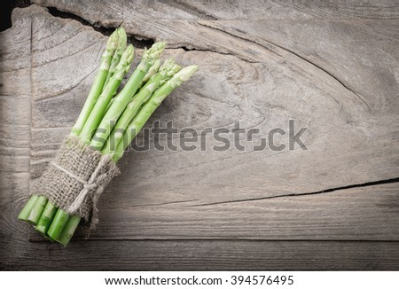 bunch of asparagus stems on brown wooden table. - stock photo