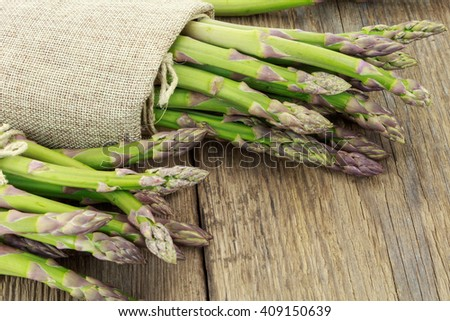 Bunch of asparagus tied with raffia cloth on wooden surface - stock photo