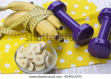 bunch of bananas, measurement tape and dumbbells