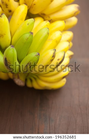 bunch of bananas on a wooden surface - stock photo