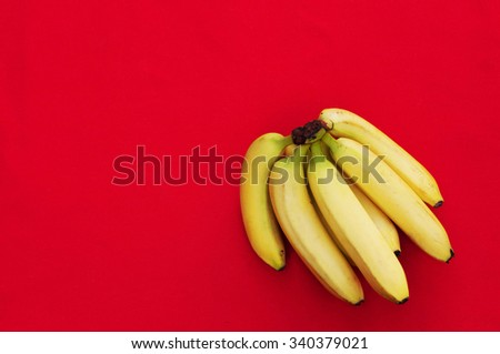 Bunch of bananas on red  background. Fresh organic Banana. Fresh bananas on  red kitchen table. Banan isolated on red.  Fresh fruits. Organic Banana. Sweet. Fruit. Food. With space for text. - stock photo