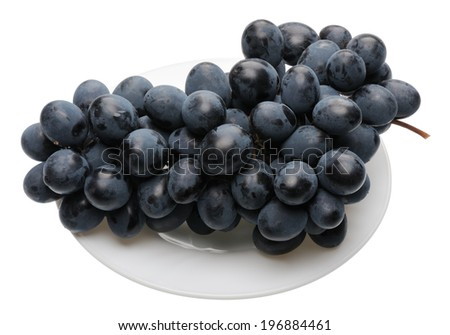 Bunch of black grapes on a white plate, isolated  - stock photo