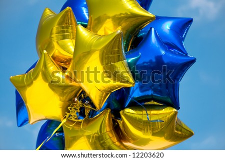 Bunch of Blue and Yellow Mylar Balloons with Sky Background - stock photo