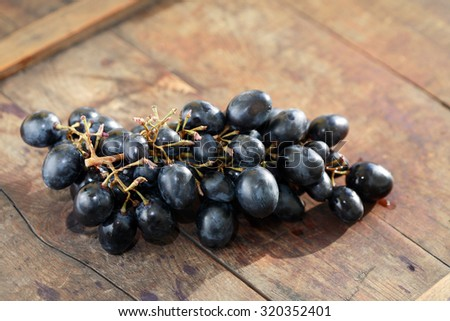 Bunch of blue grapes on nice old wooden board - stock photo