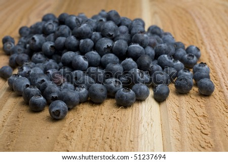 Bunch of blueberries arranged in a small pile on a cedar plank. - stock photo