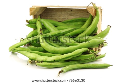 bunch of broad beans in a wooden box on a white background - stock photo