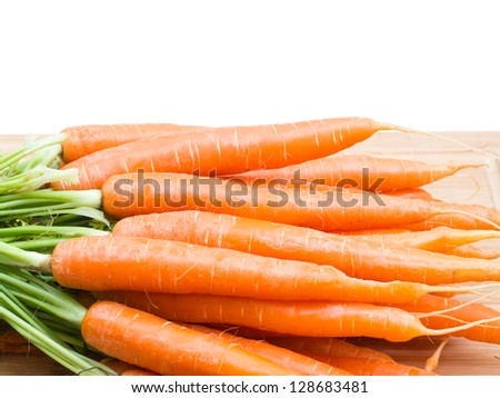 Bunch of carrots on wooden plank - stock photo