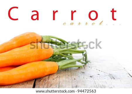 Bunch of carrots on wooden table with place for your text up - stock photo