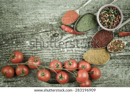 Bunch of cherry tomatoes, small bowl and antic metal spoons with different kinds of spices, sea salt and red hot chili peppers on old wooden board. Selective focus. Toned. - stock photo