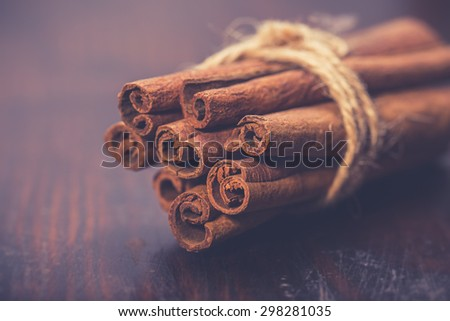 Bunch of cinnamon sticks on rustic wooden table. Vintage food photo