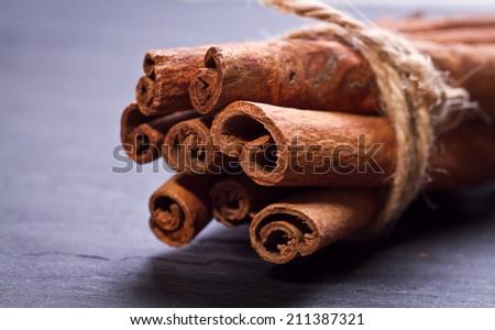 Bunch of cinnamon sticks on stones board - stock photo