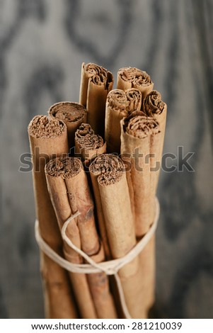 bunch of cinnamon sticks tied with twine, on rustic table - stock photo
