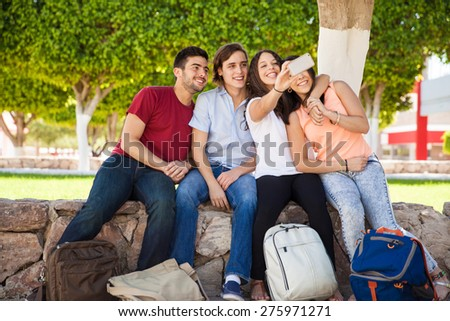 Bunch of college friends hugging each other and taking a selfie with a smartphone