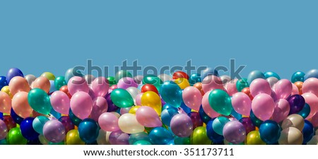 Bunch of colorful balloons border isolated on blue background - stock photo