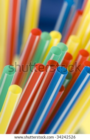 Bunch of colorful drinking straws on a bright background