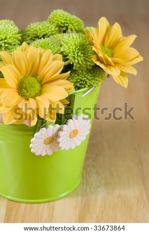 Bunch of colorful flowers arranged in little green metal bucket