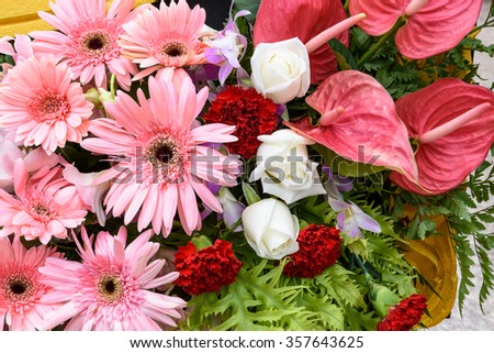 Bunch of colorful flowers, flowers bouquet including green ferns, white roses, pink gerberas, violet orchids, red carnations (dianthus caryophyllus) and pink flamingo flowers (anthurium).
