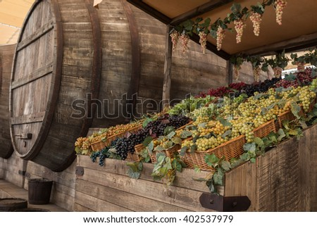 Bunch of Colorful Grapes in Wodden Basket near Big Barrel on Shelf For Sale - stock photo