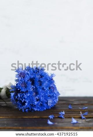 Bunch of cornflowers field. Petals on a dark table. - stock photo