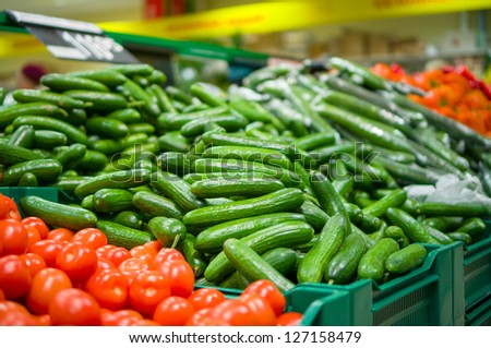 Bunch of cucumbers and tomatoes on boxes in supermarket - stock photo