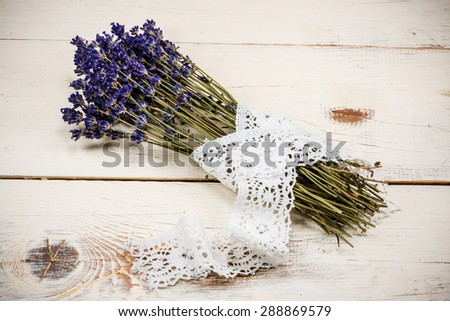 Bunch of dried lavender tied with lace placed on vintage white wooden table