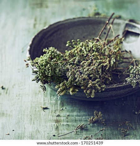 Bunch of dried wild oregano in an old bowl - stock photo